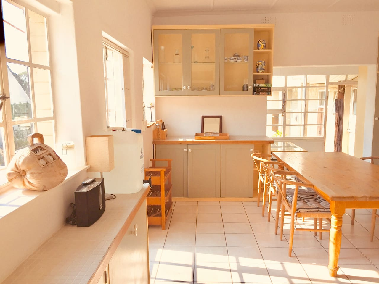 Warm sun-drenched  kitchen with french doors opening up onto patio with loungers at the pool. Barbecue facilities available.