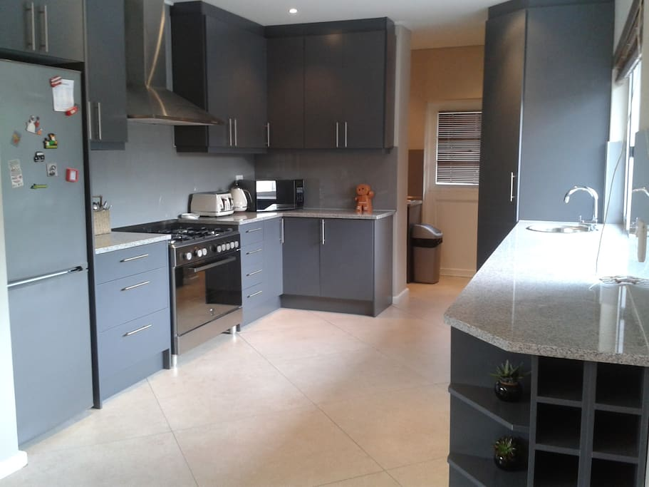 Open plan kitchen leading to separate scullery with dishwasher