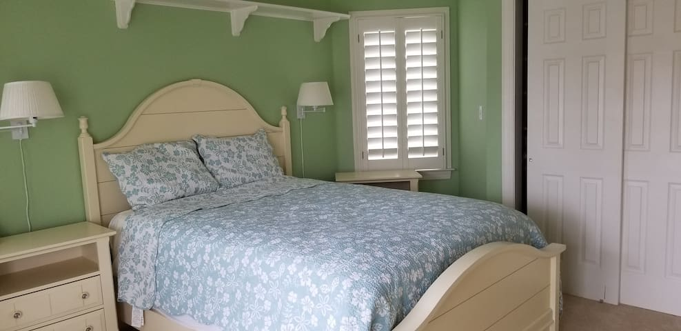 Upstairs bedroom with queen bed and attached full bathroom. Attached to outdoor balcony.