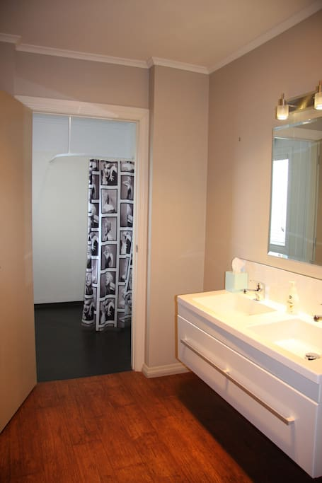 A large bathroom has double basin , shower room and separate toilet.