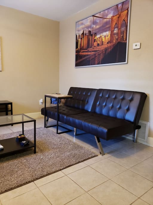Living room with futon couch and small desk for work