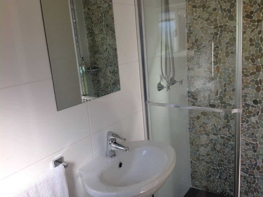 Tidy and clean bathroom with shower, toilet and basin