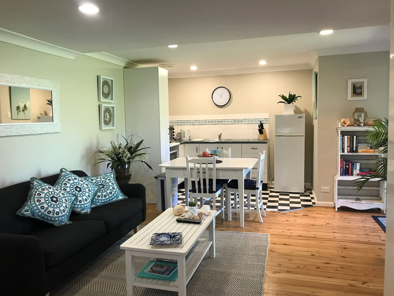 Beautifully styled with beach theme flowing throughout the apartment. This is a view of the open plan kitchen and living space. Large flat screen tv (not seen in this photo) free wifi