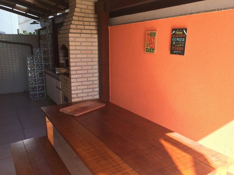 Área externa com churrasqueira e chuveiro