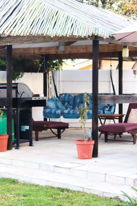 Outdoor gas barbeque. Swing and loungers in nice shade