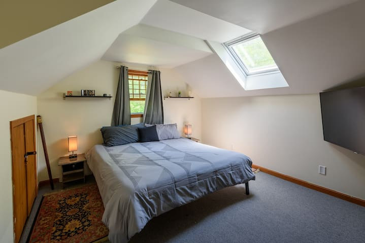 """Bedroom #3. Second floor. A 72"""" tv with Roku / Smart TV set up. King size bed."""