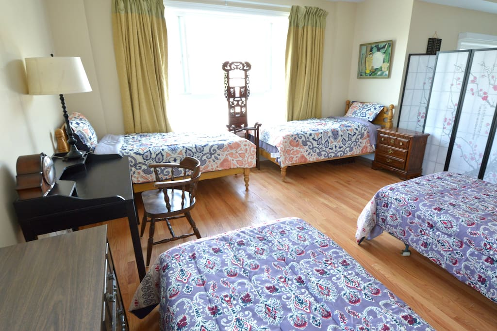 Four single beds, this previously living area is next to the dining room and kitchen, separated by room dividers