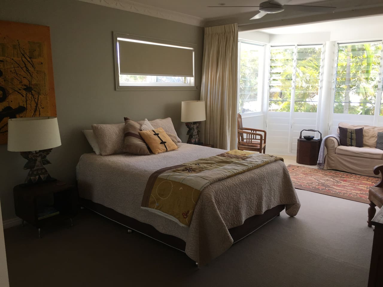 Queen size bed in peaceful setting with sitting area and desk
