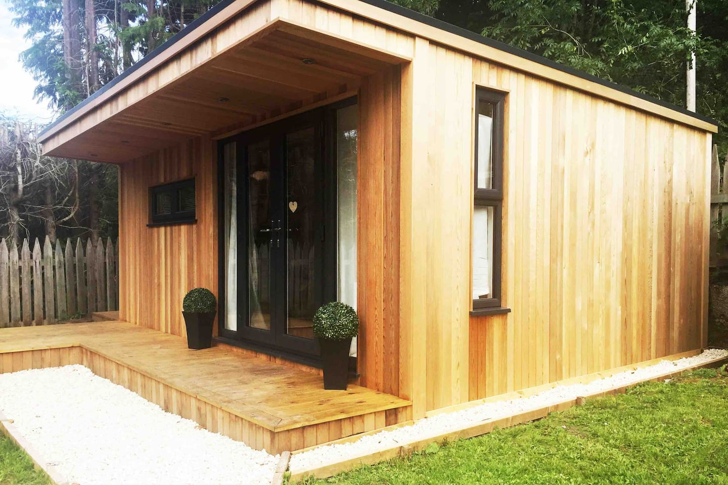 Modern Garden Room. Cedar Cladding with patio doors and open living space.