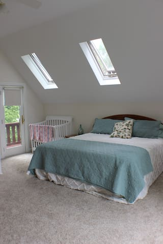 Master bedroom on 2nd floor features king bed, crib, skylights, and deck overlooking the lake