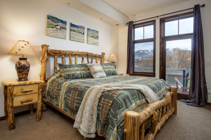 Main bedroom with cozy aspen king bed and access to balcony.  Welcome to the Mountains!