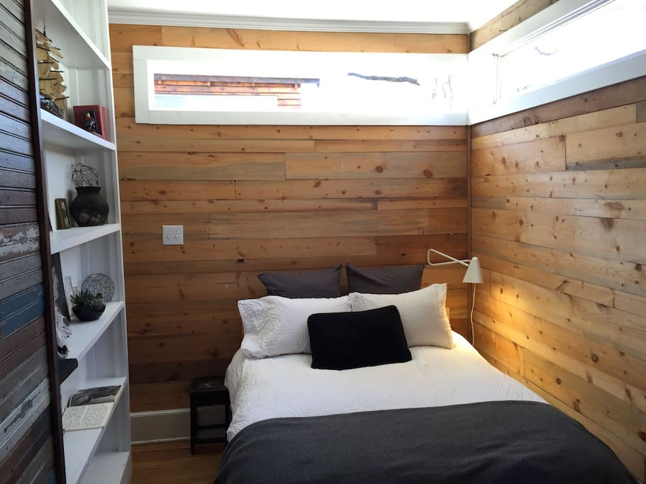 The bedroom wooden walls and high windows for nice light.