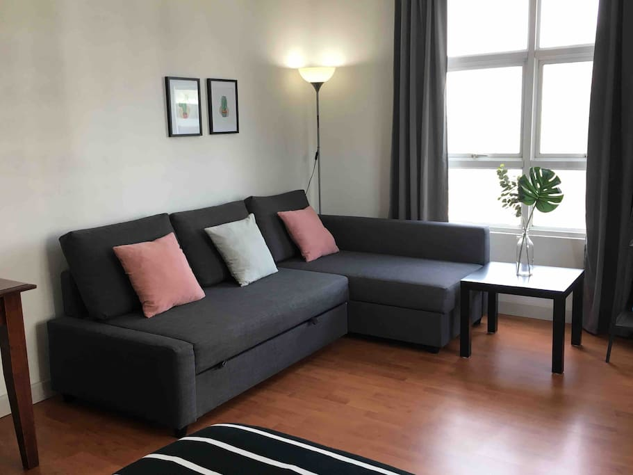 Large sofa bed next to window with city view