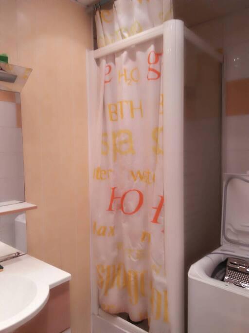 Salle de bain avec douche, lavabo et lave-linge