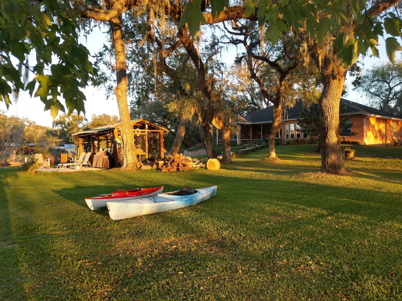 BBQ area with fire pit. Backyard with kayaks.