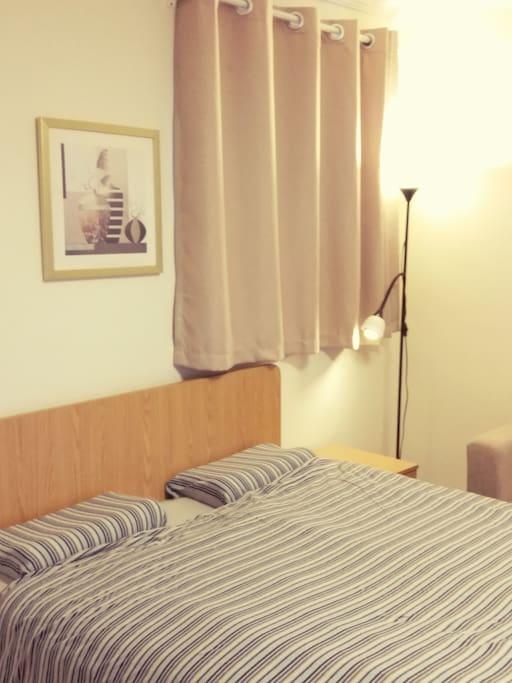 这里是双人床,落地灯有大小两个,当你准备休息了,你可以只开小的那个,它可以旋转,向床或向沙发