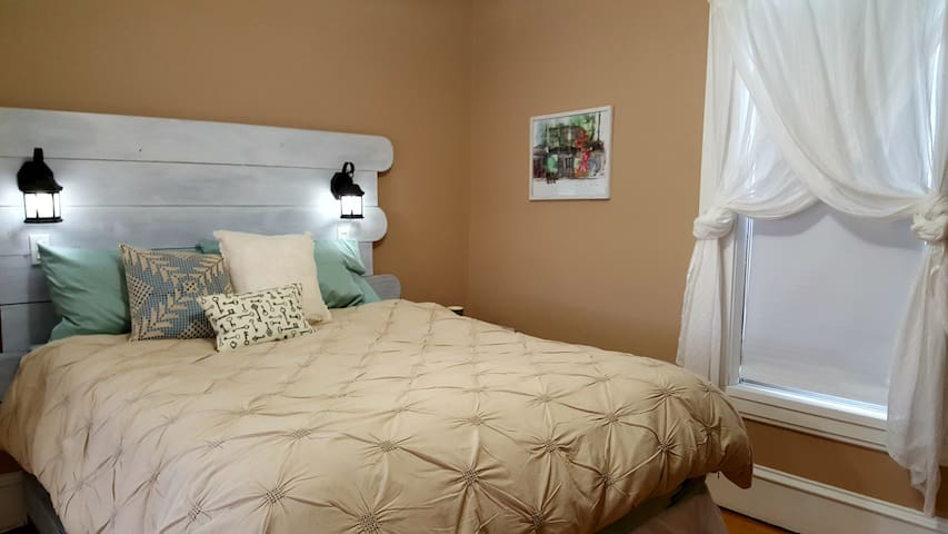 Charming main bedroom featuring a queen bed with memory foam mattress topper