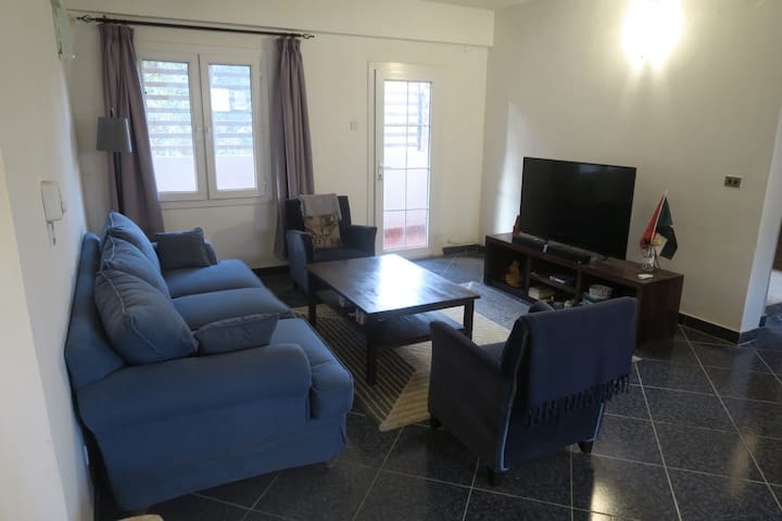 Fully furnished living room with large very comfortable couch, two single sweaters, large coffee table and new entertainement system consisting of 55 inch flat screen and satellite receiver. With lots of lights and access to balcony.