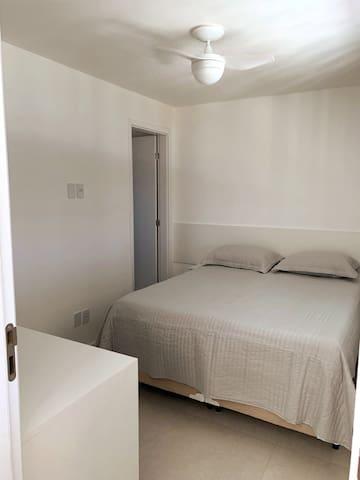 Quarto - 1 com banheiro, cama de casal, ar condicionado e ventilador de teto, guarda roupa, cortina.