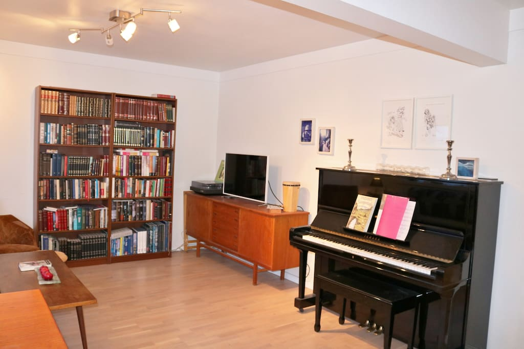 Part of the living room. Yamaha Piano, TV and a record player. Inside the sideboard is a stereo music centre