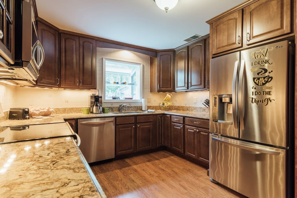 Kitchen with dishwasher, range, microwave, fridge, coffee maker, cooking and serving dishes and utencils
