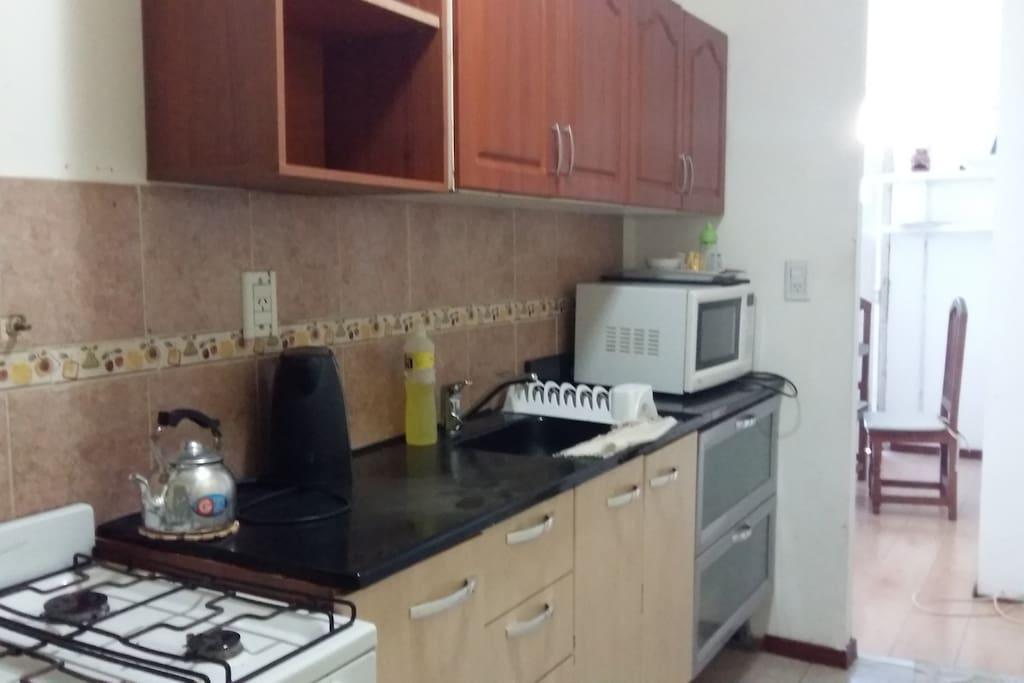 Cocina equipada con vajilla ,microondas y pava eléctrica.