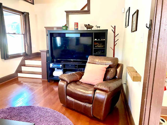 """There's your 55"""" TV with surround sound in the entertainment center there next to the coat stand in the corner.  That recliner is perfect for naps and you can see the staircase that leads up to the bathroom and bedroom."""