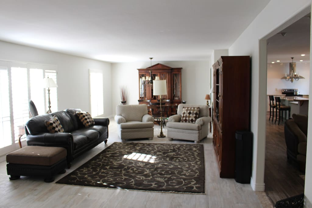 Large living/dining room with lots of natural light from large windows, expensive, wood-look tile flooring, comfy leather couch and Ethan Allen chairs.