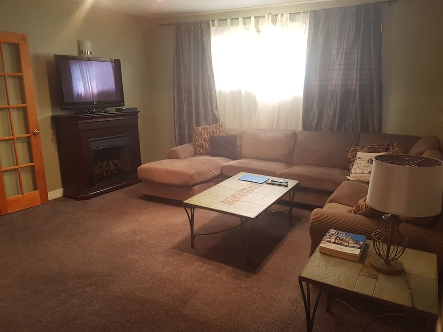Large comfy sectional with electric fireplace and TV