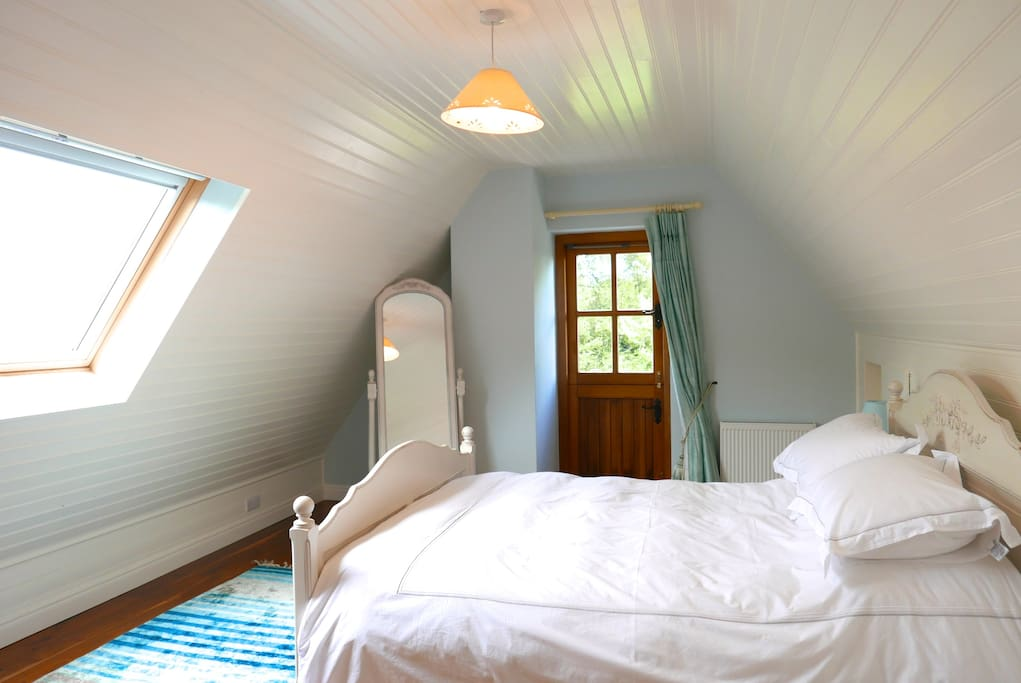 Master bedroom with views of the mountains and a private deck with steps to the garden.