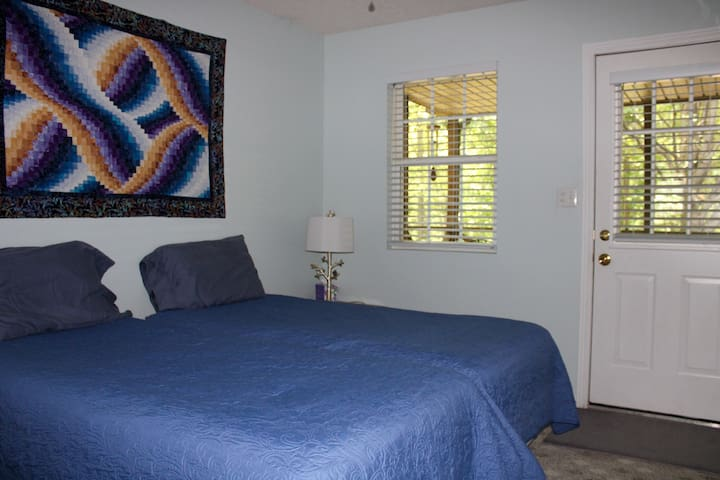 The second bedroom features two twin beds along with TV and access to the back screened-in porch and hot tub.