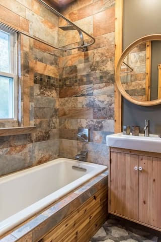 Gorgeous newly renovated bathroom with rainwater shower head and soaking tub