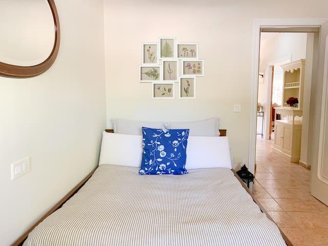 Dormitorio con cama de matrimonio y vistas al jardín.