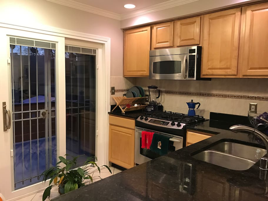 Spacious kitchen with granite countertops, oven, stove, fridge, freezer, various coffee makers, and stand mixer.