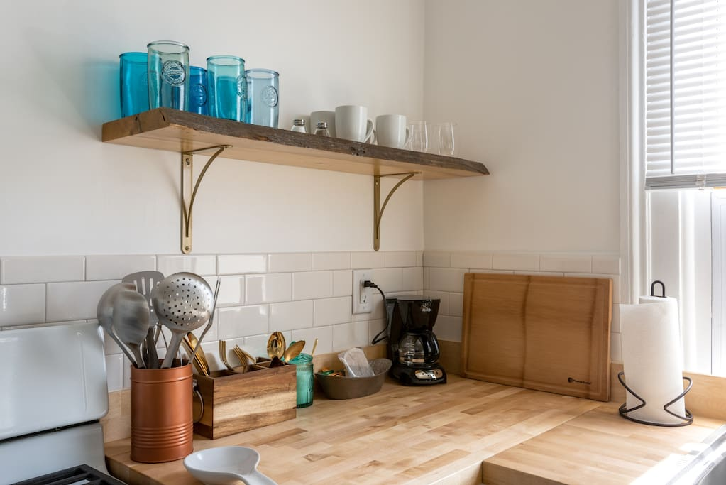 Well-stocked with blue-green glassware and gold flatware. Custom-built live-edge wood shelving!