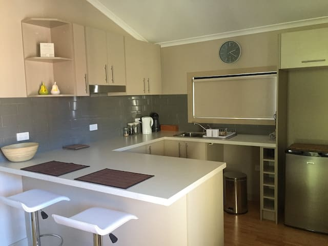 A modern kitchen with cooking facilities ( Hot plates and Microwave ) and a convenient breakfast bar.