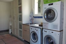 Separate utilityroom with two washingmachines and a tumbledryer