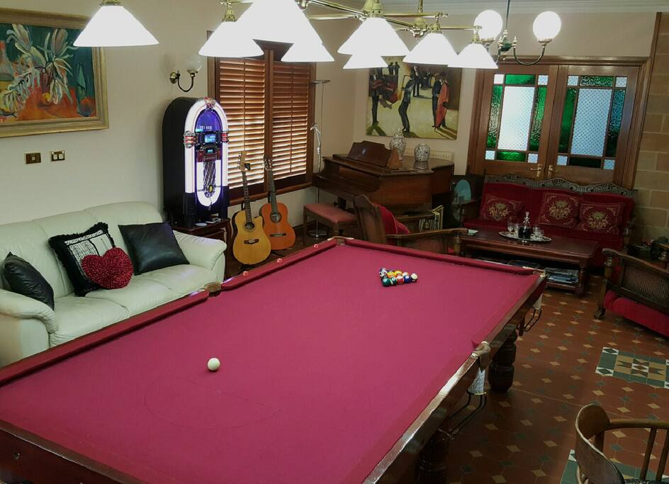 Pool/Music room piano and guitars. Jukebox plays CD's and other media.