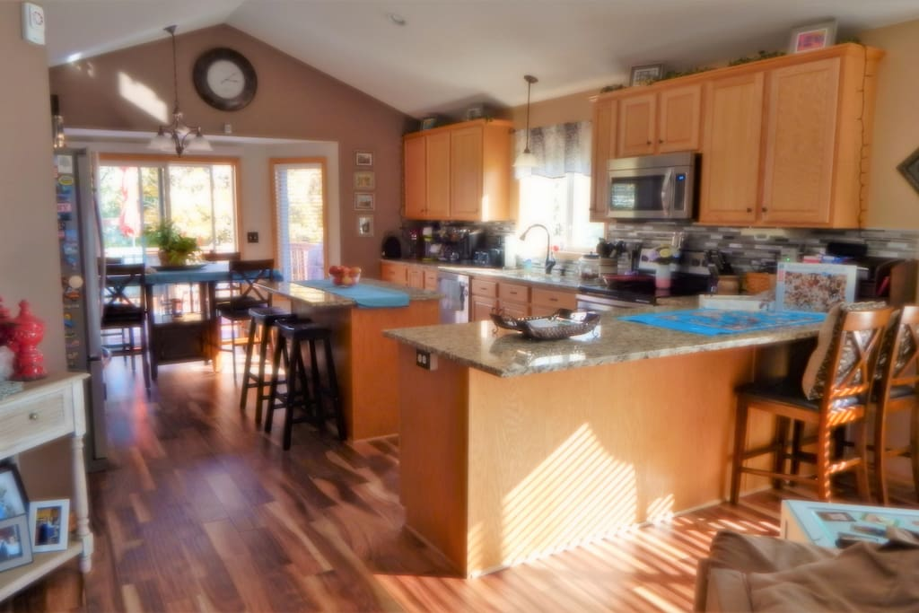 Open kitchen leads to upper deck with outdoor gas grill