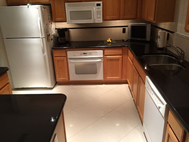 Kitchen with Granite counter tops built in Appliances oven and flat glass stove top, Microwave with Vent