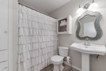 Upstairs full bathroom features a full sized tub, and a pedestal sink... so cute!