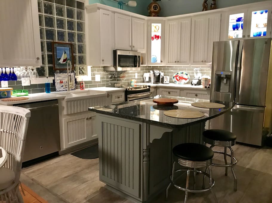Tastefully furnished kitchen with all new appliances- stove, dishwasher, microwave, & refrigerator. Bar sits two people & adjacent dining table sits 5 or 6.
