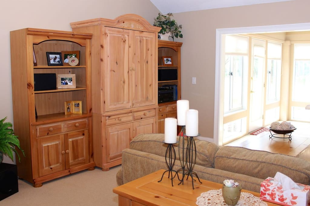 A beautiful wall unit armoir fills the living room.