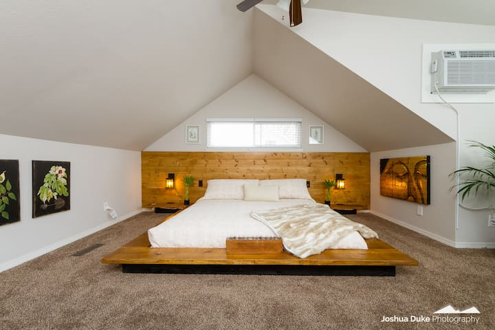 """Our upstairs """"zen"""" room is guaranteed to create the calming atmosphere after adventuring downtown.  Custom handmade king sized wooden bedframe with built-in lamp lights and additional remote controlled lights under the bed?! Dreams do come true."""