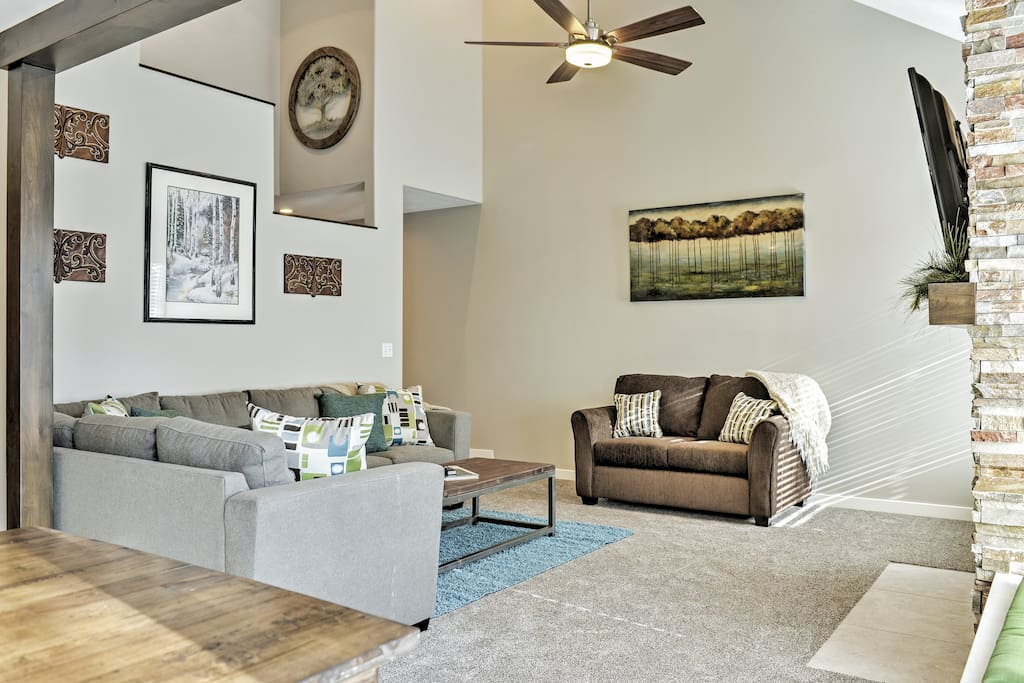 Sink into the plush furnishings in the living room featuring a soaring ceiling.