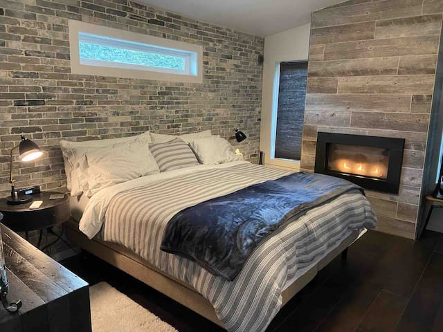 Master bedroom with Serta iMotion adjustable California King, dreamy fireplace, and large flat screen smart TV.