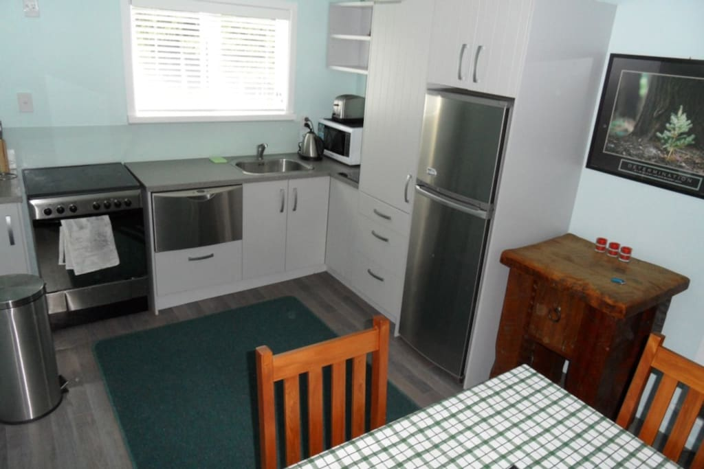 A modern kitchen and dining room with dishwasher, fridge-freezer, microwave, oven and stove-top.