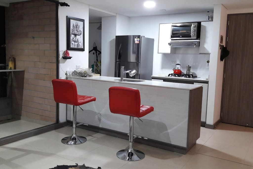 Kitchen area accommodated with cooking utensils, toaster oven and seating area