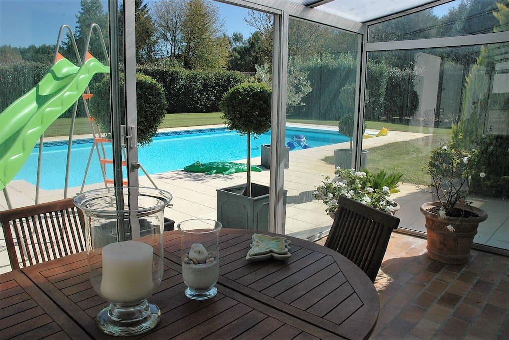 Véranda vue sur piscine et jardin