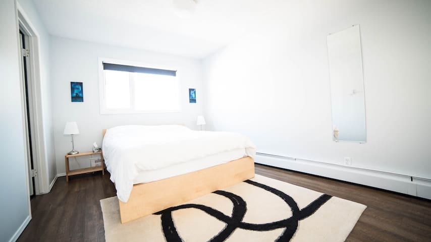 This room features a comfy queen sized bed and private half bathroom with a toilet and sink.